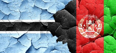 Botswana flag with afghanistan flag on a grunge cracked wall