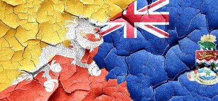 cayman: Bhutan flag with Cayman islands flag on a grunge cracked wall Stock Photo