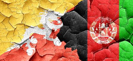 afghanistan flag: Bhutan flag with afghanistan flag on a grunge cracked wall