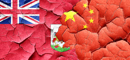 bermuda: bermuda flag with China flag on a grunge cracked wall Stock Photo