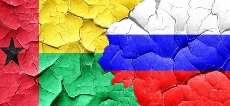 guinea bissau: Guinea bissau flag with Russia flag on a grunge cracked wall Stock Photo