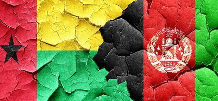 afghanistan flag: Guinea bissau flag with afghanistan flag on a grunge cracked wall