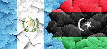 bandera de guatemala: guatemala flag with Libya flag on a grunge cracked wall