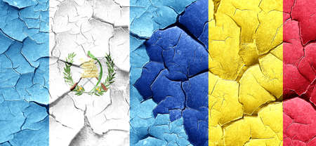 flag of guatemala: guatemala flag with Romania flag on a grunge cracked wall