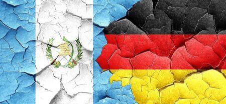 bandera de guatemala: bandera de Guatemala con la bandera de Alemania en una pared agrietada grunge Foto de archivo