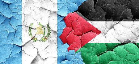 palestine: guatemala flag with Palestine flag on a grunge cracked wall