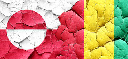 greenland: greenland flag with Guinea flag on a grunge cracked wall