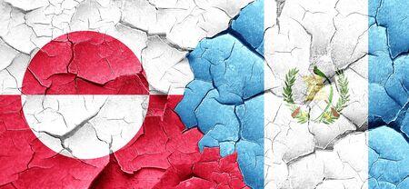 bandera de guatemala: Bandera de Groenlandia con la bandera de Guatemala en una pared agrietada grunge Foto de archivo