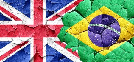 england politics: Great britain flag with Brazil flag on a grunge cracked wall