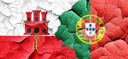 portugese: gibraltar flag with Portugal flag on a grunge cracked wall