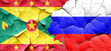 grenada: Grenada flag with Russia flag on a grunge cracked wall Stock Photo