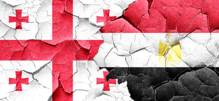 bandera egipto: bandera de Georgia con la bandera de Egipto en una pared agrietada grunge