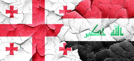 iraq war: Georgia flag with Iraq flag on a grunge cracked wall