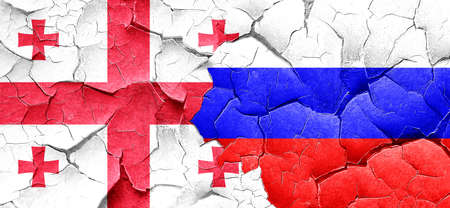 georgia flag: Georgia flag with Russia flag on a grunge cracked wall