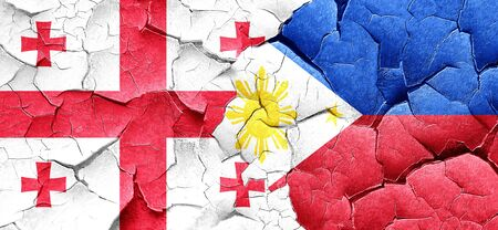 georgia flag: Georgia flag with Philippines flag on a grunge cracked wall Stock Photo
