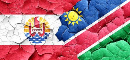 polynesia: french polynesia flag with Namibia flag on a grunge cracked wall