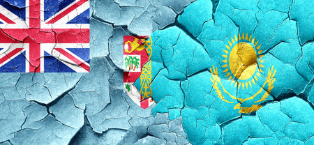 fiji: Fiji flag with Kazakhstan flag on a grunge cracked wall Stock Photo