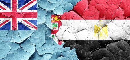 egypt flag: Fiji flag with egypt flag on a grunge cracked wall