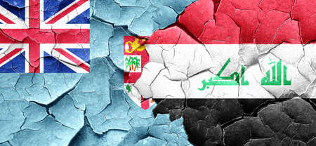 iraq conflict: Fiji flag with Iraq flag on a grunge cracked wall