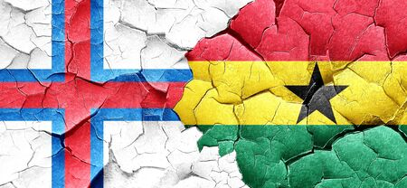 ghanese: faroe islands flag with Ghana flag on a grunge cracked wall