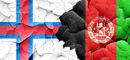 afghanistan flag: faroe islands flag with afghanistan flag on a grunge cracked wall Stock Photo
