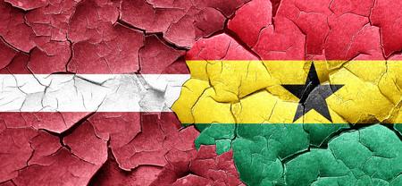 ghanese: Latvia flag with Ghana flag on a grunge cracked wall Stock Photo