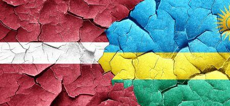 latvia flag: Latvia flag with rwanda flag on a grunge cracked wall