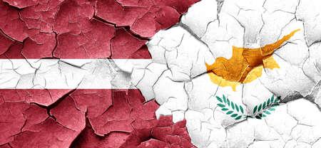 latvia flag: Latvia flag with Cyprus flag on a grunge cracked wall