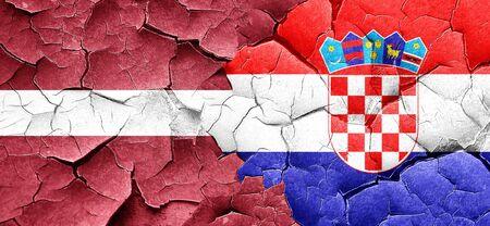 croatia flag: Latvia flag with Croatia flag on a grunge cracked wall