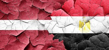 bandera de egipto: bandera de Letonia con la bandera de Egipto en una pared agrietada grunge Foto de archivo