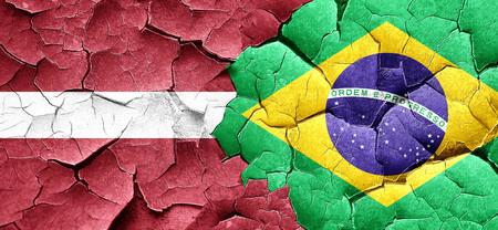 latvia flag: Latvia flag with Brazil flag on a grunge cracked wall
