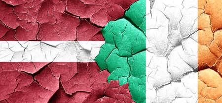 latvia flag: Latvia flag with Ireland flag on a grunge cracked wall Stock Photo