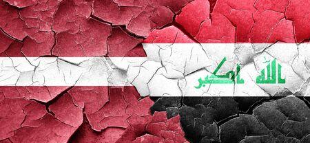 iraq war: Latvia flag with Iraq flag on a grunge cracked wall