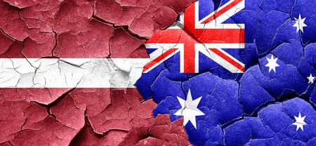 australian culture: Latvia flag with Australia flag on a grunge cracked wall Stock Photo