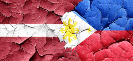 philippino: Latvia flag with Philippines flag on a grunge cracked wall