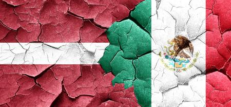 latvia flag: Latvia flag with Mexico flag on a grunge cracked wall Stock Photo