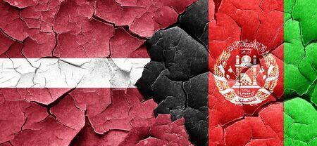 latvia flag: Latvia flag with afghanistan flag on a grunge cracked wall Stock Photo