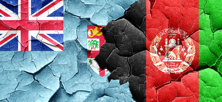 Fiji flag with afghanistan flag on a grunge cracked wall