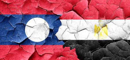 egypt flag: Laos flag with egypt flag on a grunge cracked wall