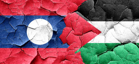 cracked wall: Laos flag with Palestine flag on a grunge cracked wall Stock Photo