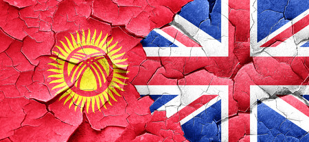 england politics: Kyrgyzstan flag with Great Britain flag on a grunge cracked wall