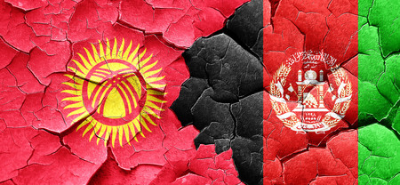 Kyrgyzstan flag with afghanistan flag on a grunge cracked wall Stock Photo