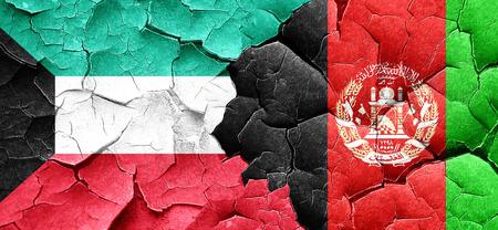 afghanistan flag: Kuwait flag with afghanistan flag on a grunge cracked wall