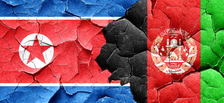 afghan: North Korea flag with afghanistan flag on a grunge cracked wall
