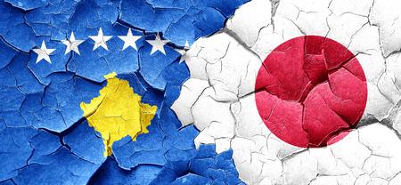 kosovo: Kosovo flag with Japan flag on a grunge cracked wall