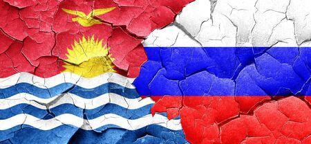 kiribati: Kiribati flag with Russia flag on a grunge cracked wall Stock Photo