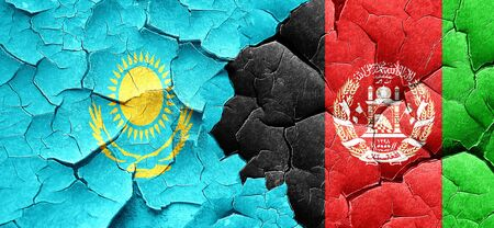 Kazakhstan flag with afghanistan flag on a grunge cracked wall