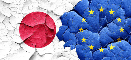 european culture: Japan flag with european union flag on a grunge cracked wall