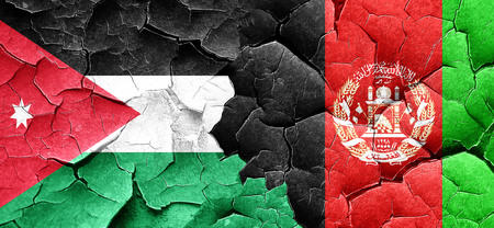 afghanistan flag: Jordan flag with afghanistan flag on a grunge cracked wall