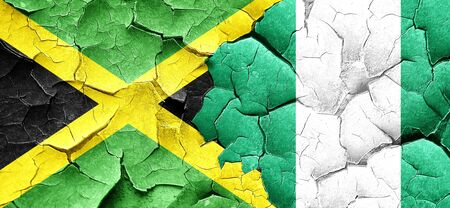 nigerian: Jamaica flag with Nigeria flag on a grunge cracked wall Stock Photo